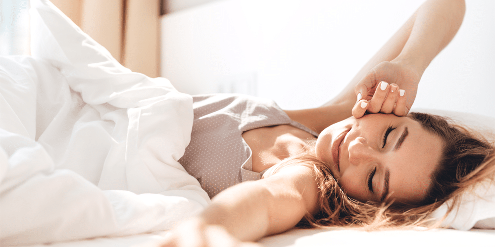 Woman stretching after a full night of sleep on a great natural latex mattress