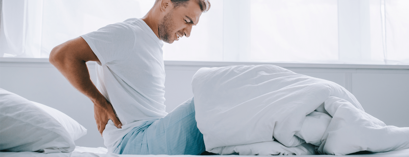 a man on a bed holding his back is a sign on How to tell if your bed is causing back pain