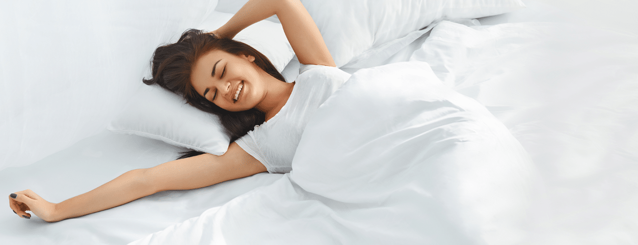 a woman is smiling while lying down on her bed How to tell if your bed is causing back pain