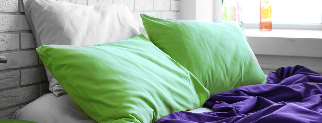 white and green cooling pillows on a bed